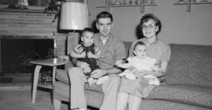 1950s nuclear family sitting on couch