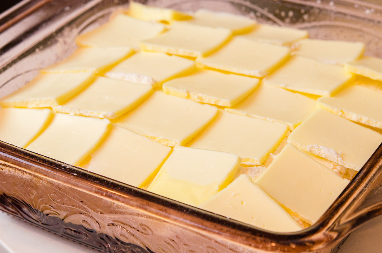 Take butter slices and place in a single layer over the cake mix, trying to cover as much of the cake as possible.