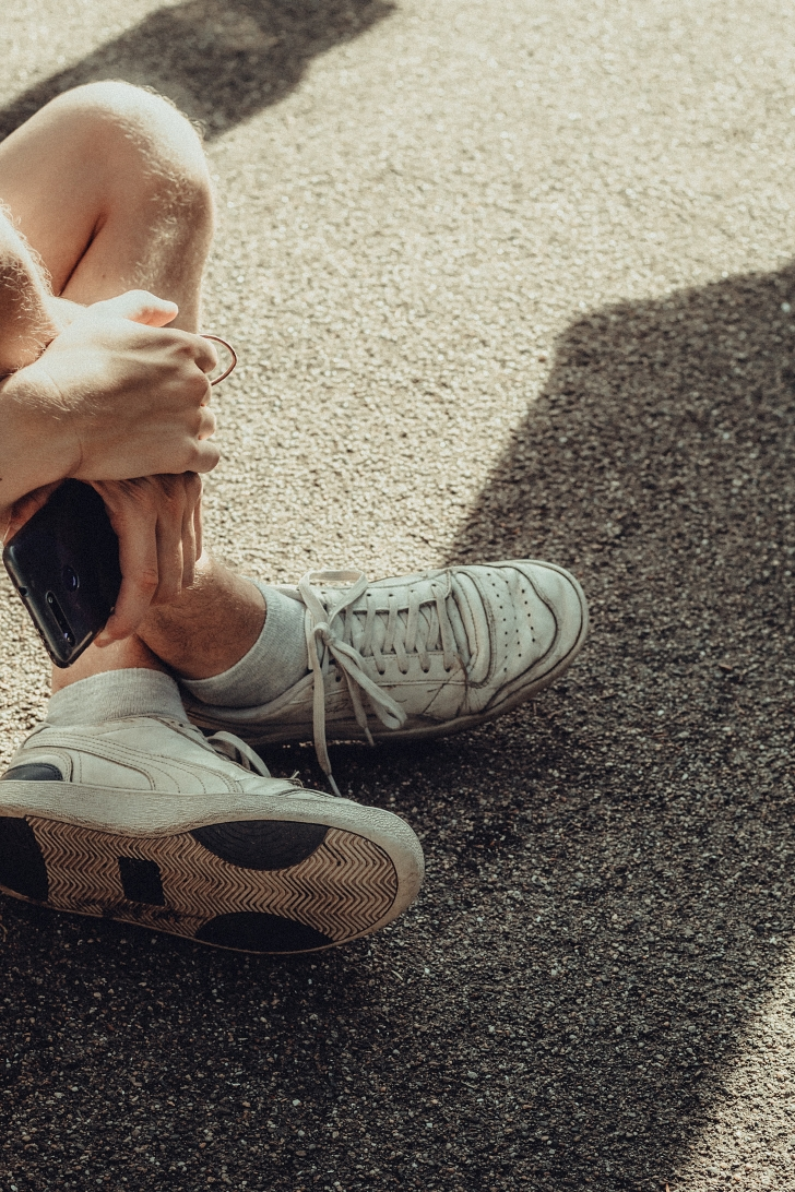 person with worn sneakers sitting on ground
