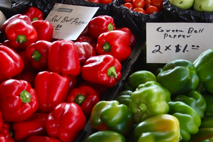 red and green bell peppers being sold in a market