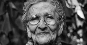 elderly woman with an expressive face wearing glasses