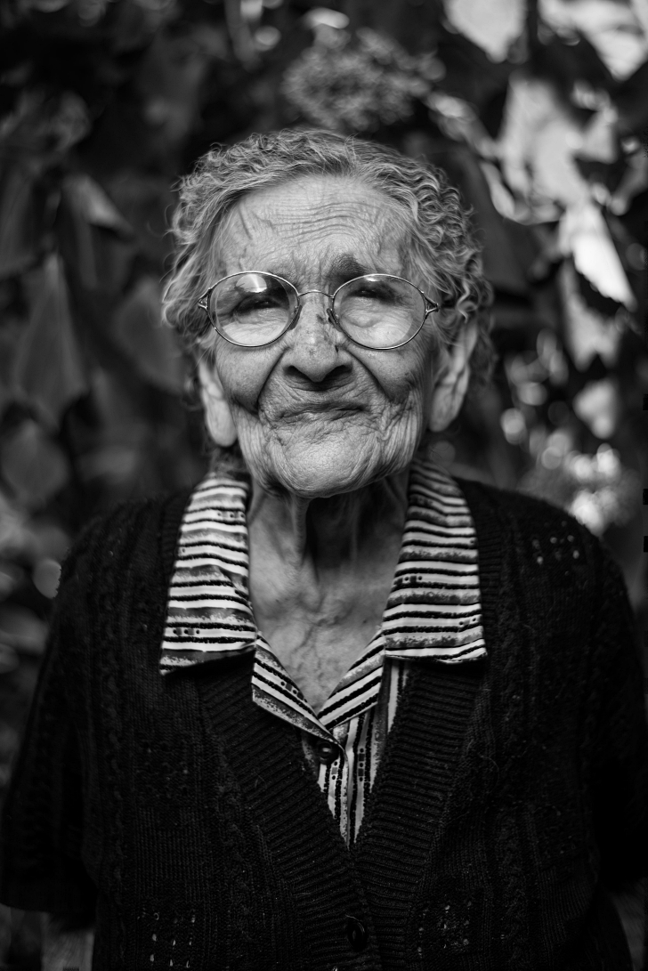 elderly woman with glasses and an expressive face