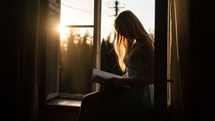 woman reading a book indoors at sunset