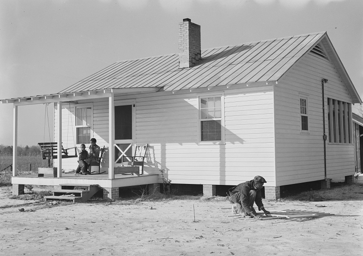 African American family in front of their new house, 1930s