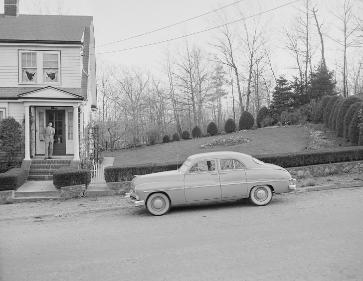 1950s house and car with man standing on porch