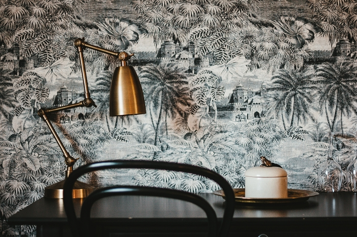 toile wallpaper with modern brass lamp