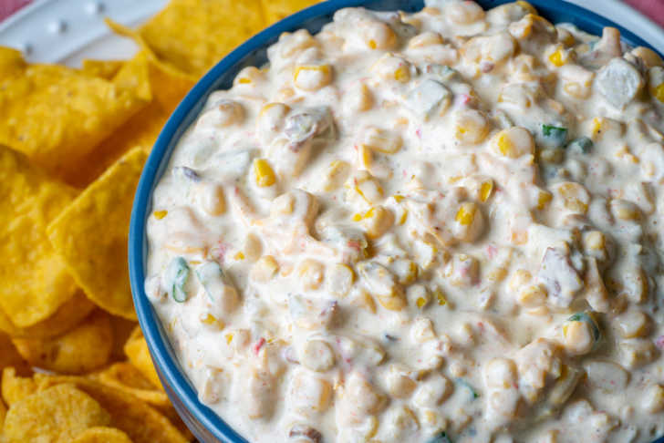 CLose up of creamy corn dip with chips in the background