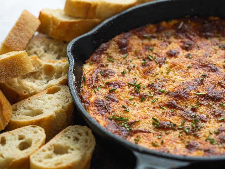Baked cheese in a skillet surrounded by chips