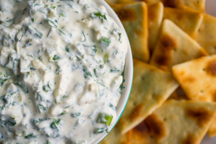 Close up of creamy dip with green onions in it