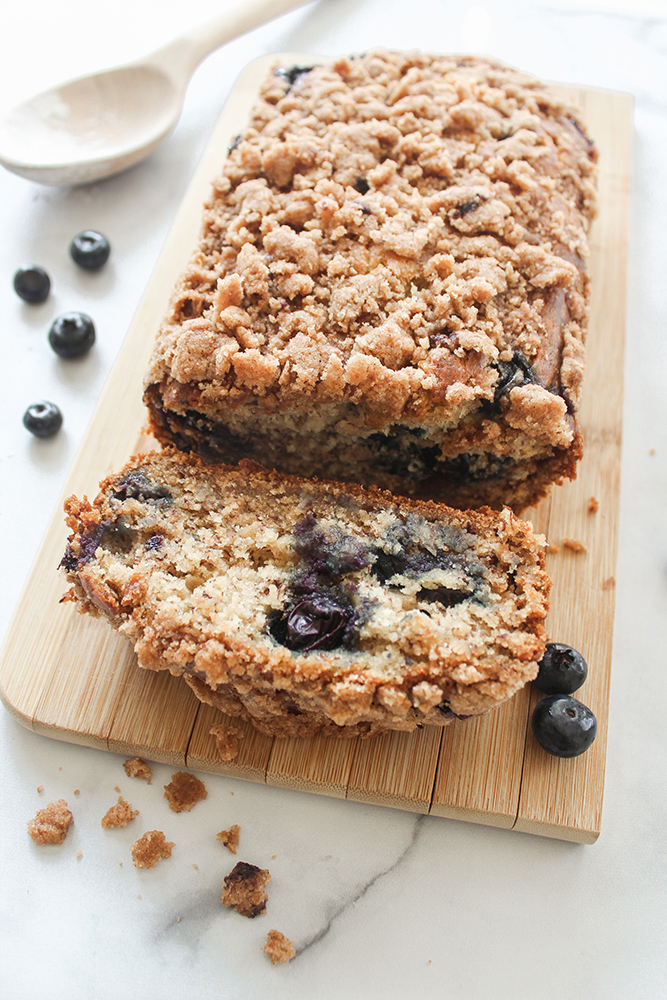 Close up of blueberry bread with one slice flat in front of the loaf