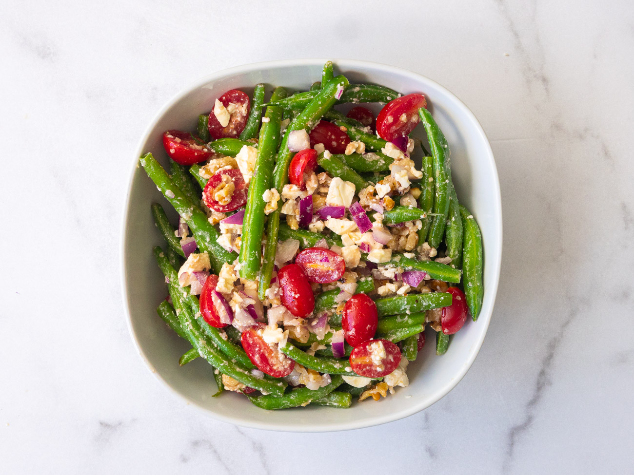 Top down photo of green beans, feta cheese, tomatoes, and walnuts in a bowl