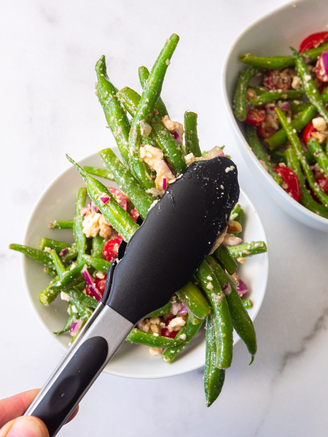 Tongs holding green bean salad over a serving dish