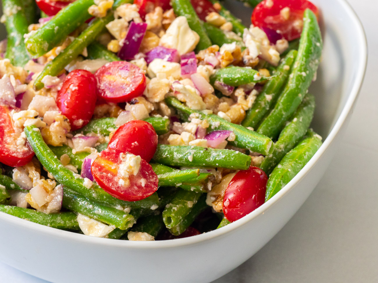 Green beans, cherry tomatoes, feta, and walnuts in a bowl with vinaigrette