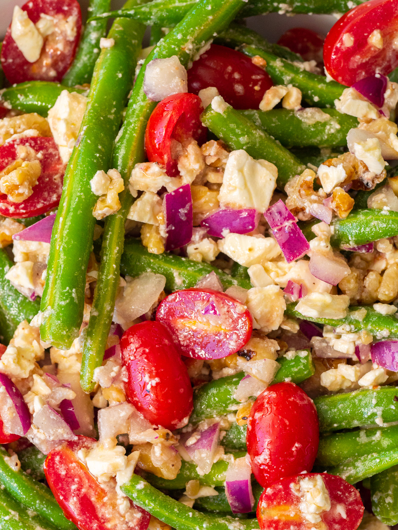 Extreme close-up of green bean salad with beans, tomatoes, feta, and walnuts