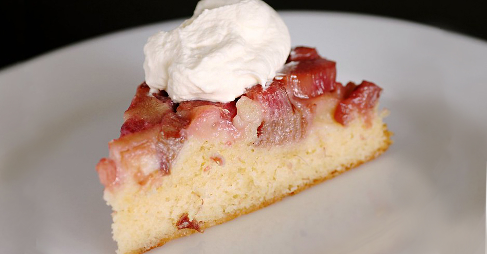 Strawberry rhubarb upside down cake slice with whipped cream on top