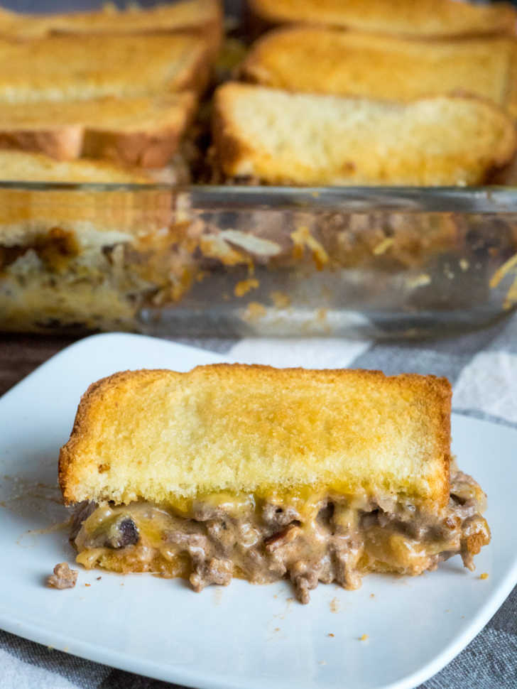 Photo of grilled cheese sandwich cut in half with meat sauce in the middle. Casserole dish in the background.