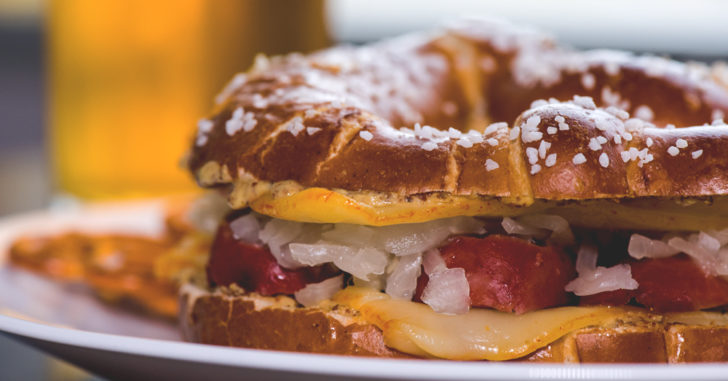Pretzel bread sandwich with cheese, bratwurst, saurkraut, and sauce.