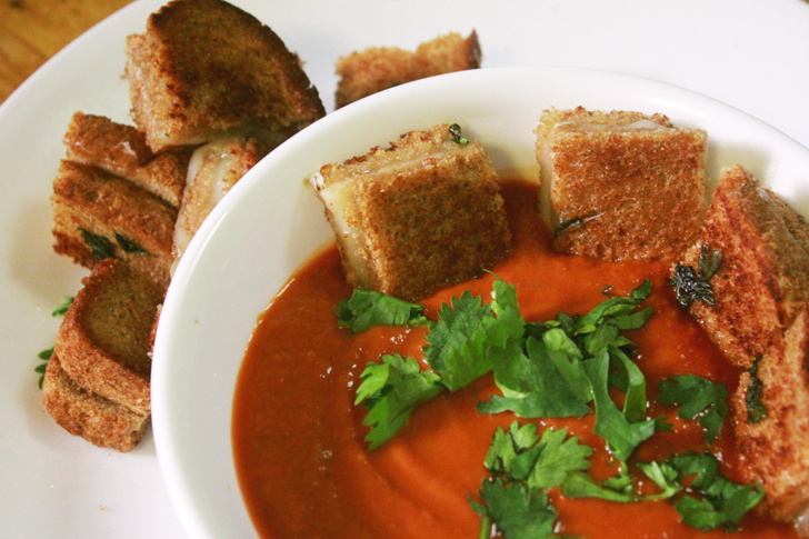 Top down image of a bowl of tomato soup with little square grilled cheese sandwiches as croutons.
