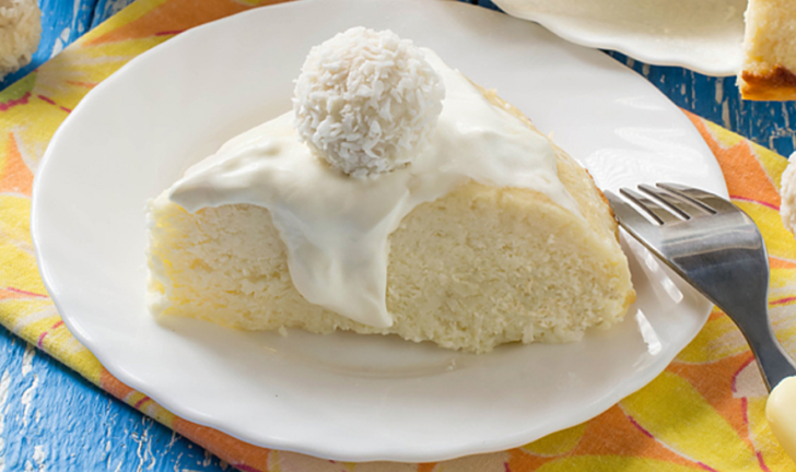 Slice of white cake with white frosting and a coconut truffle on top.