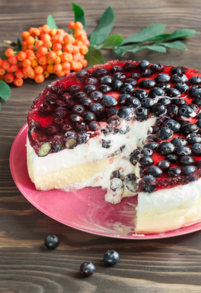 Side view of blueberry cheesecake with a slice cut out of it.