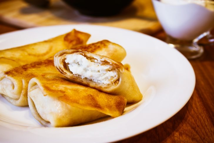 Thin rolled pancakes with cottage cheese center stacked on a plate.