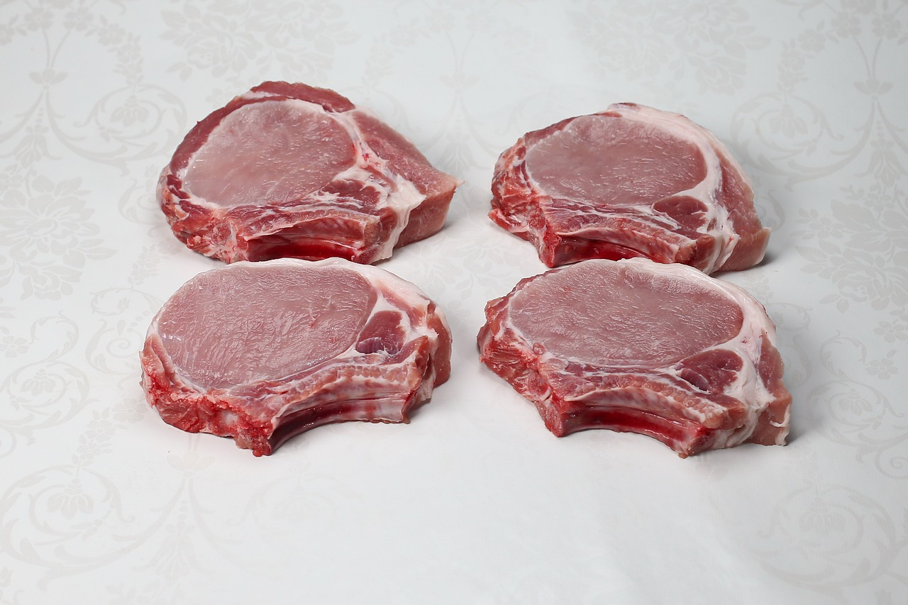 Four raw pork chops on a white background.