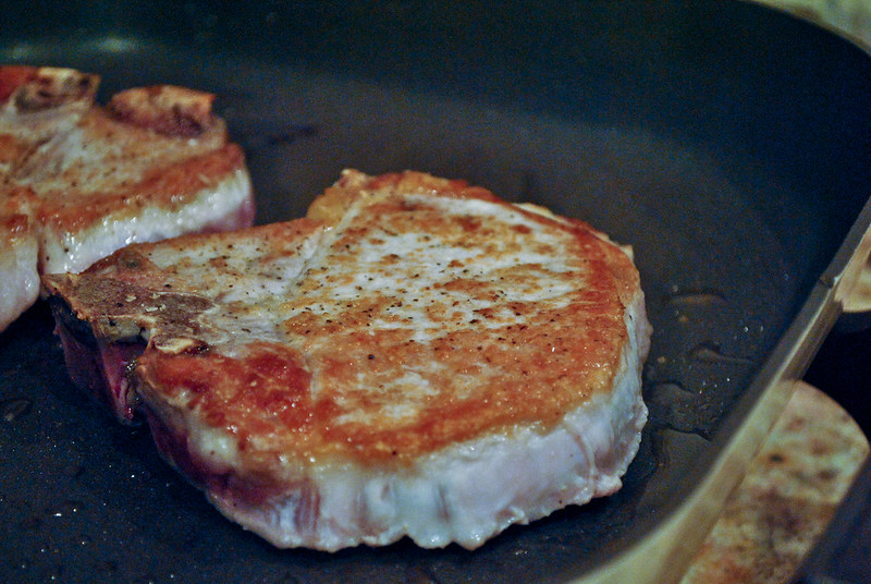 Close up of pork chop in a skillet, slightly browned on top.