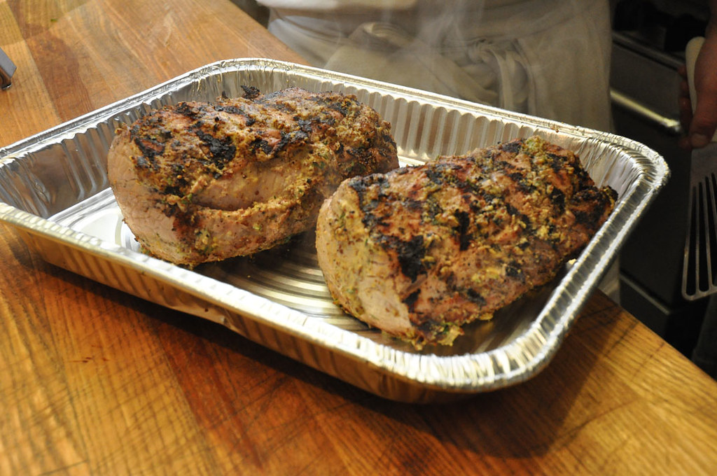 Two cooked and seasoned pork loins in a pan.