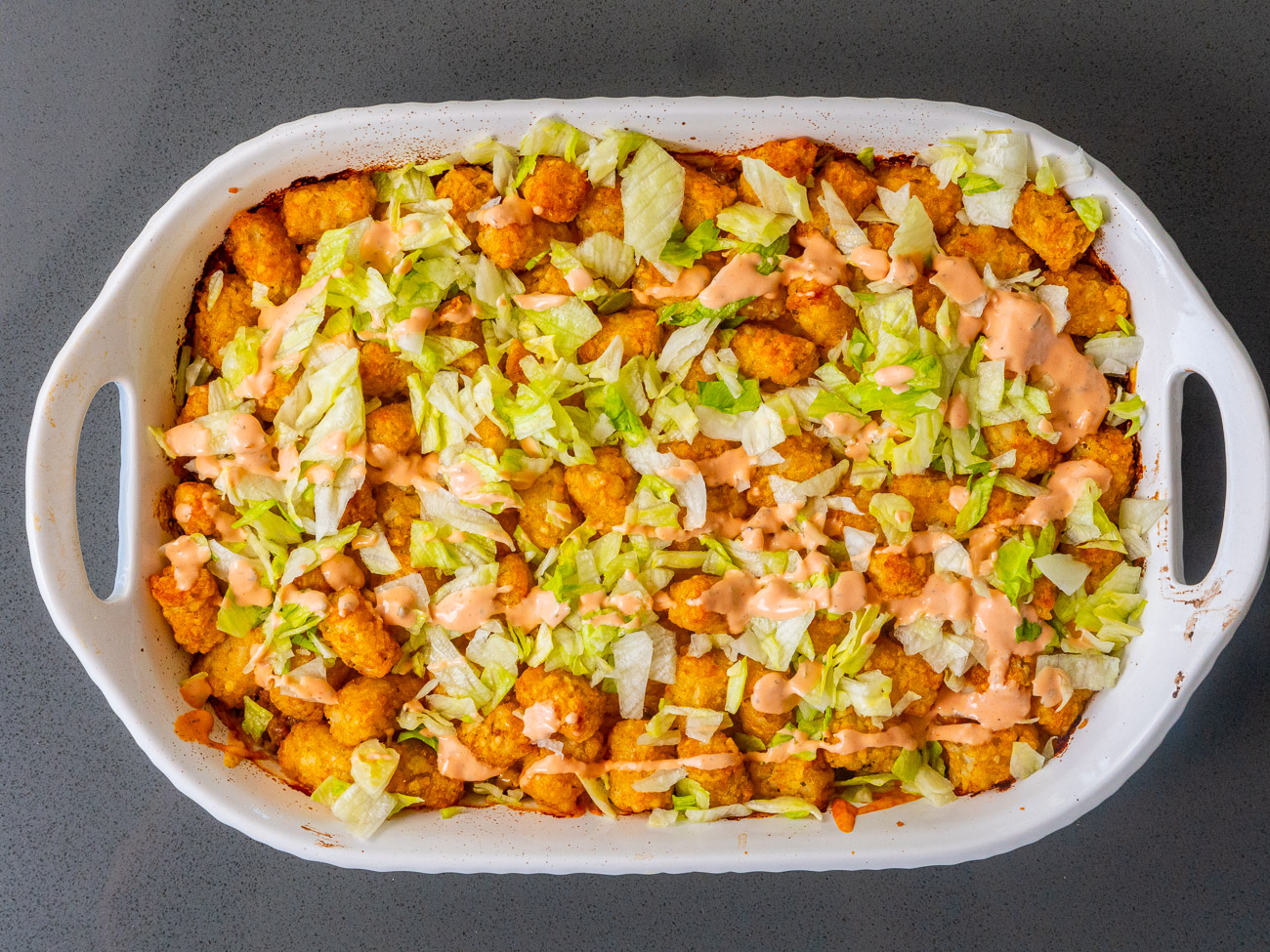 Top down shot of big mac tater tot casserole in a white dish.
