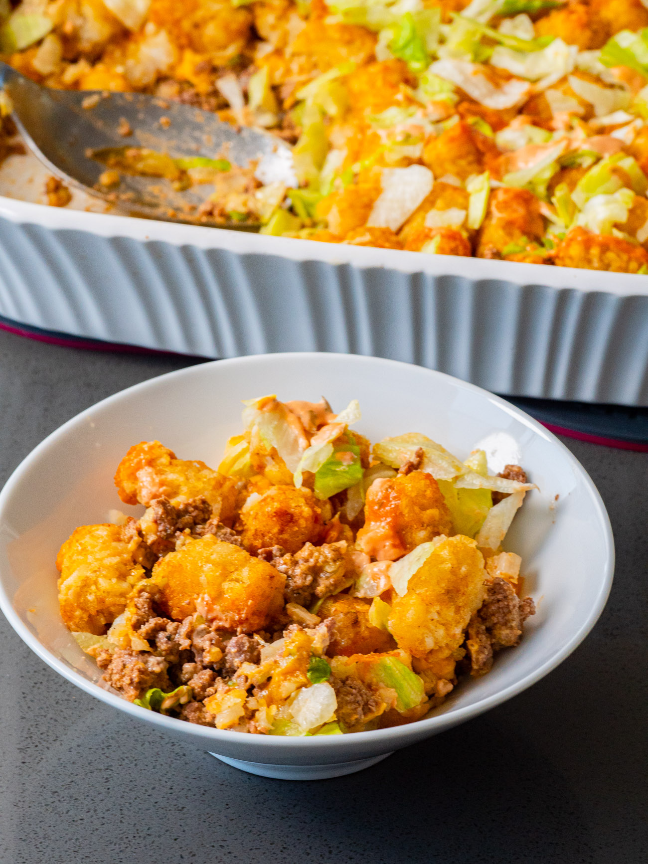 A serving of tater tot casserole on a plate with garnish.