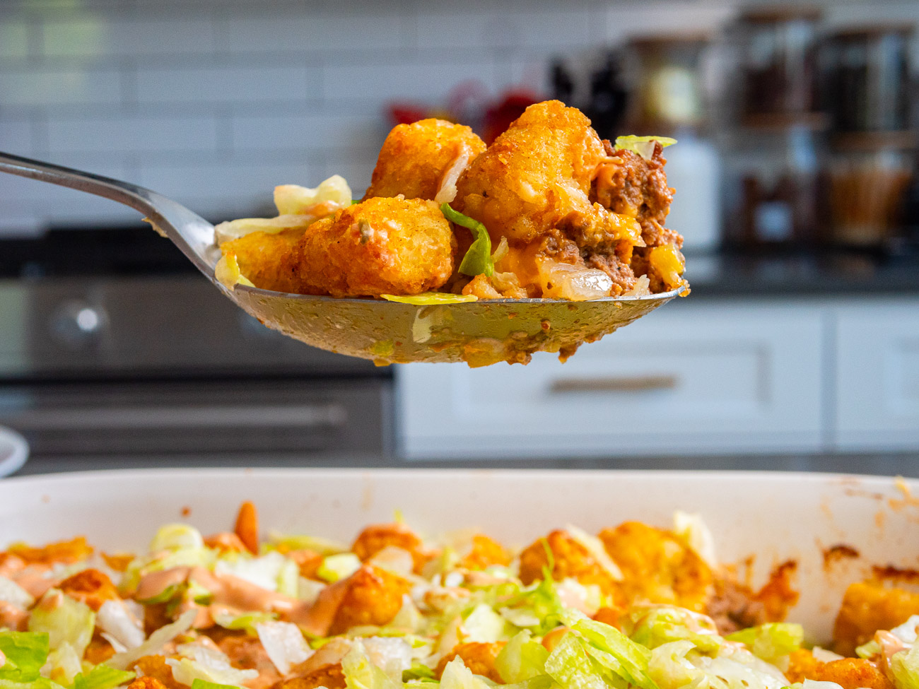 Side view of a big scoop of tater tot casserole.