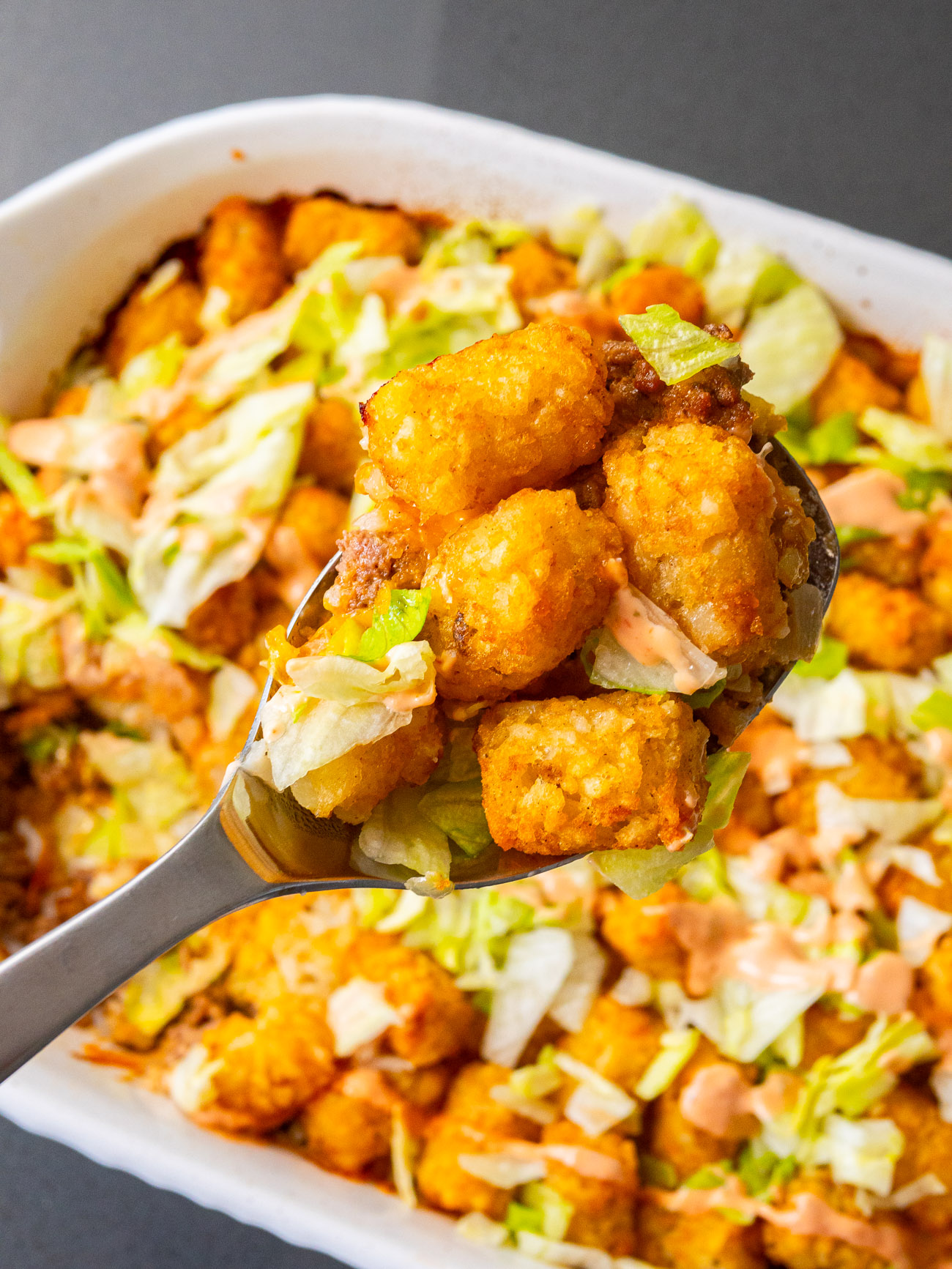 Top down view of a big scoop of tater tot casserole.