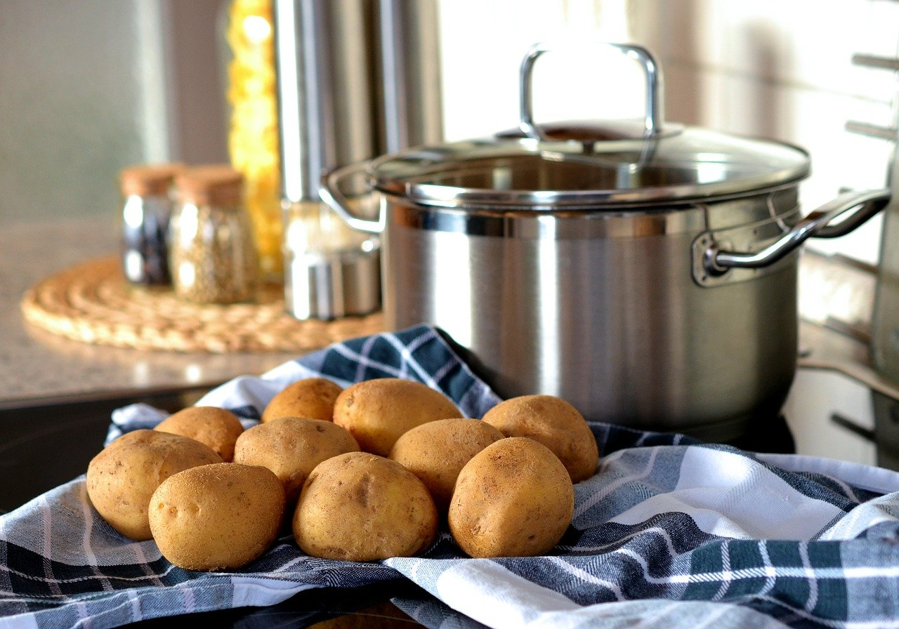 Potatoes next to a pot sitting on a counter