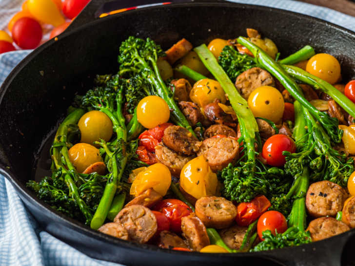 Close up of sausage, tomatoes, and broccoli in a skillet