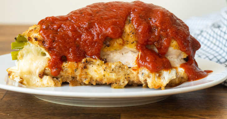 Plate with breaded chicken breast and sauce on top