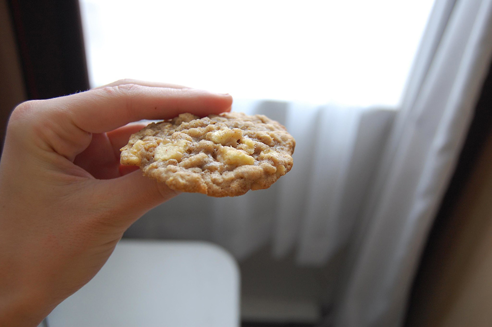 Persong holding oatmeal cookie and taking a side shot