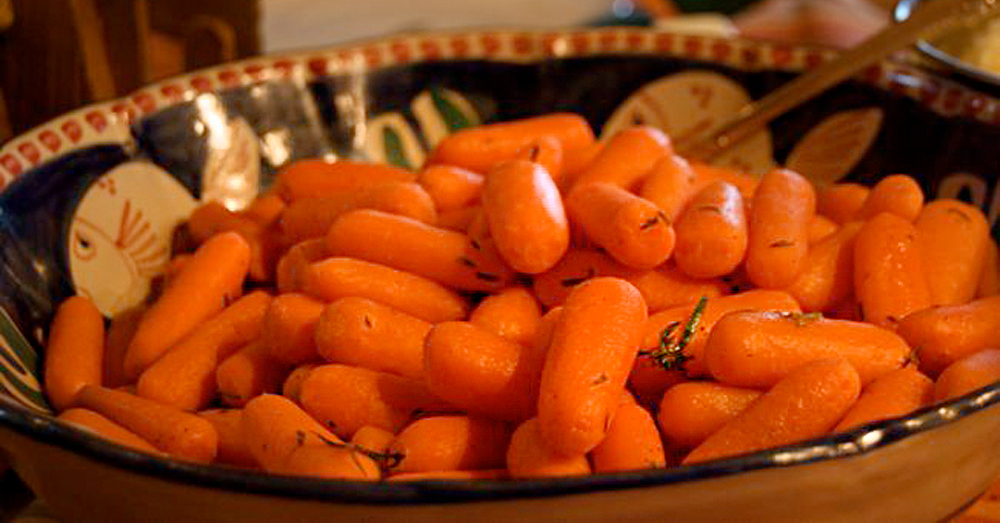Side shot of cooked carrots in a bowl