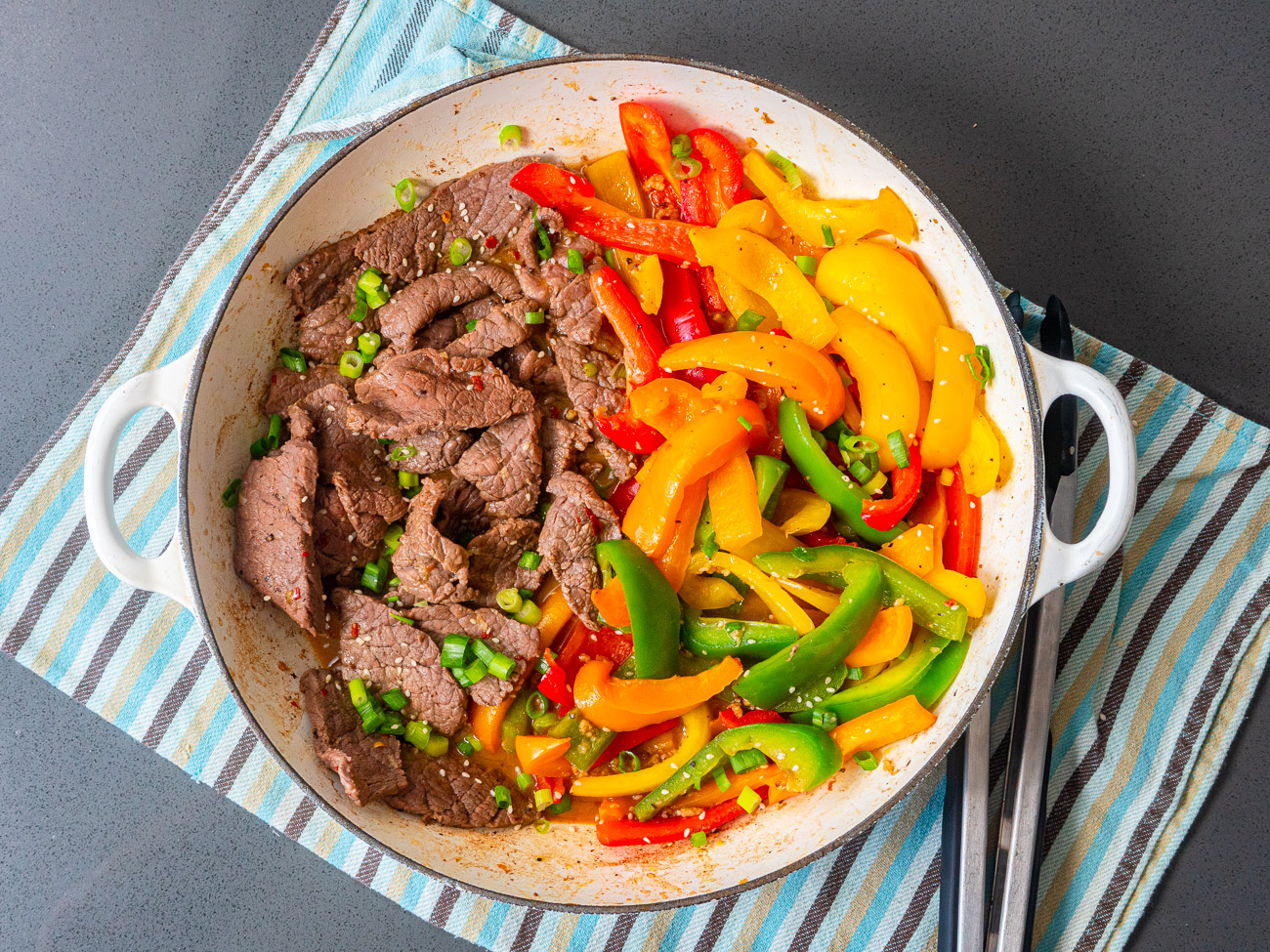 Top down of peppers and steak in a skillet