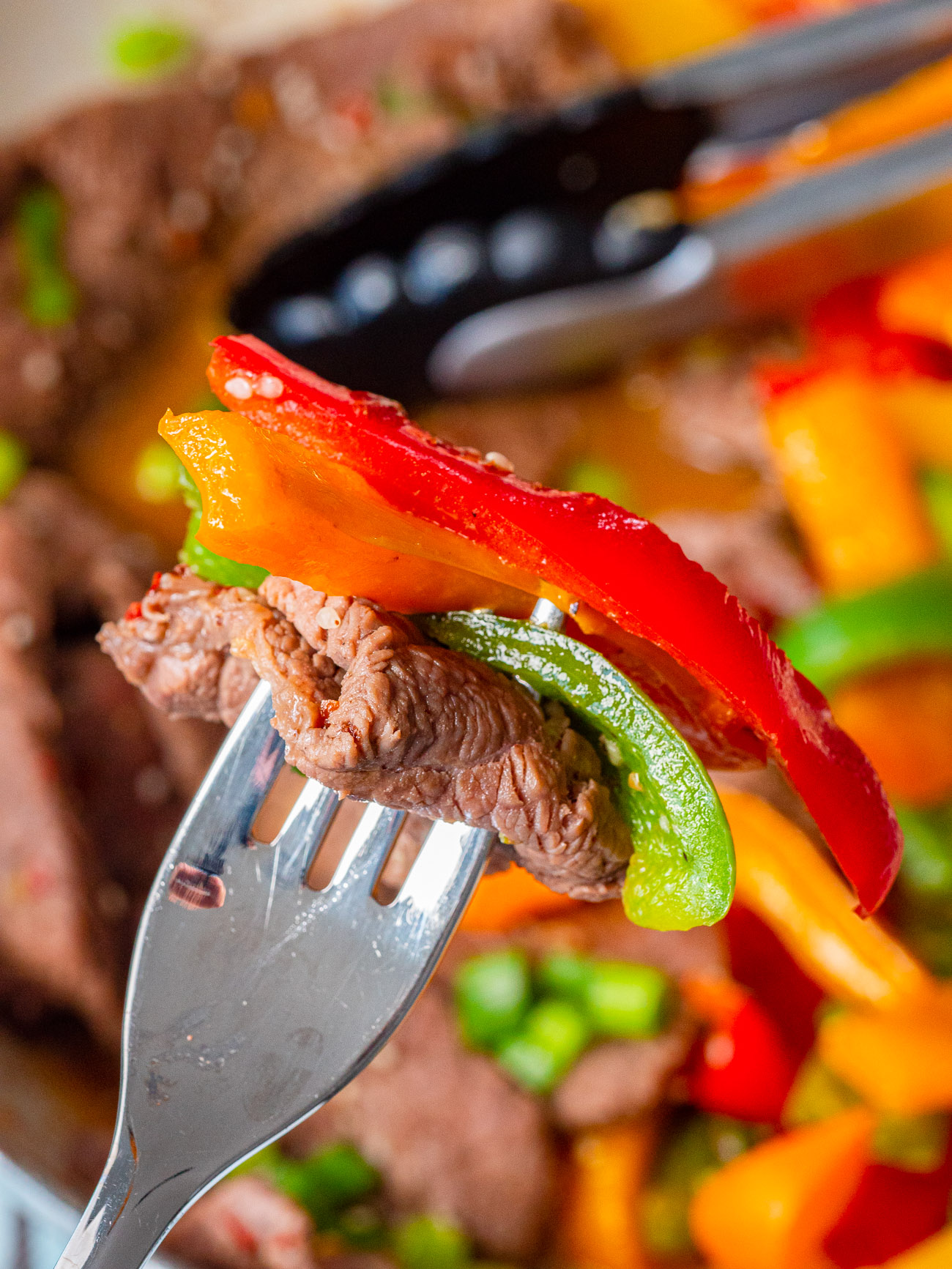 Close up of a forkful of steak and peppers