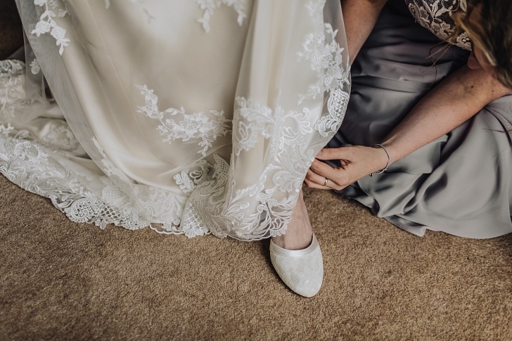 bridesmaid prepares bride for wedding