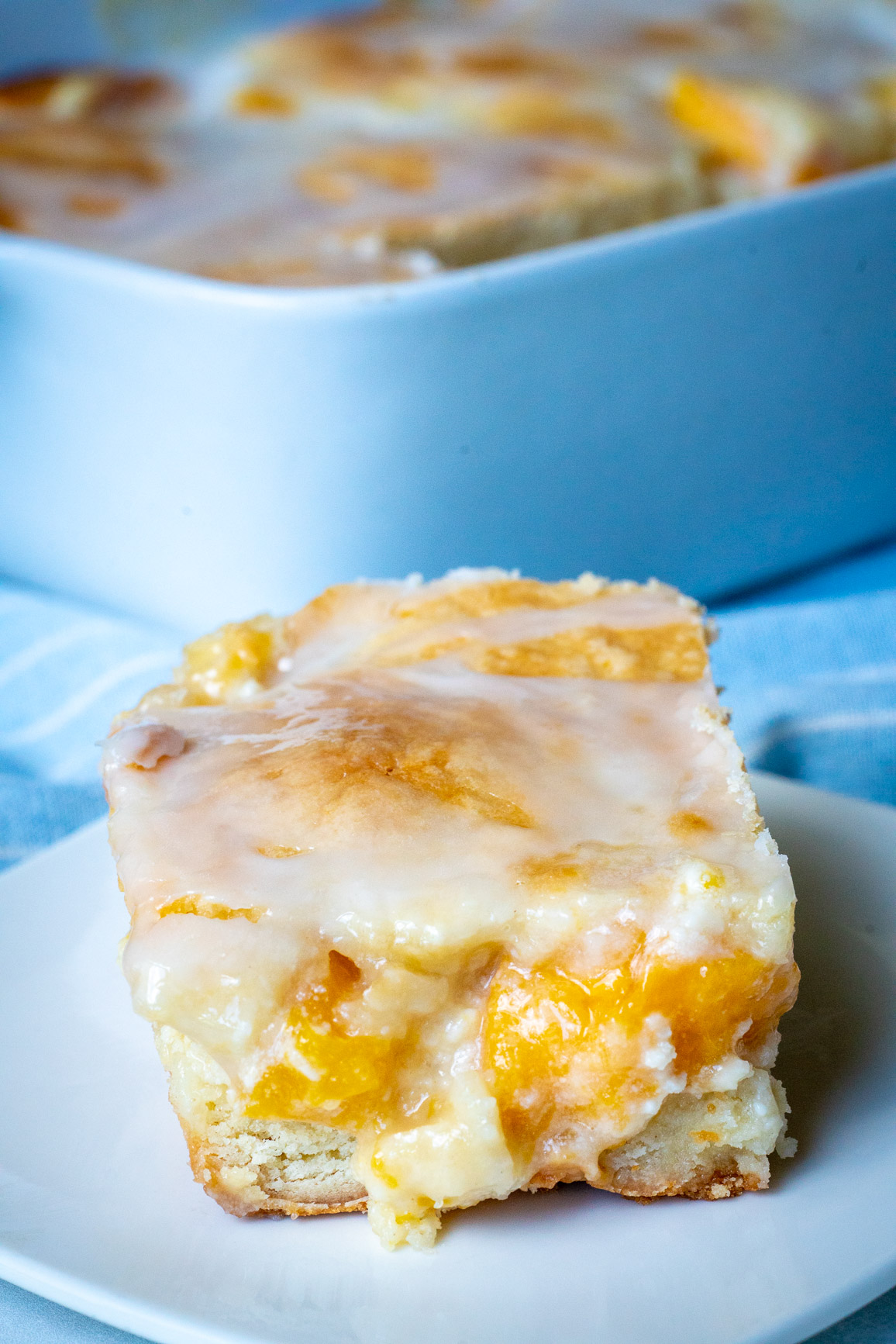 Close up of peaches and cream bars with pan in the background