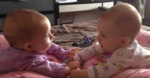 twin babies talking and holding hands