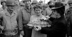 "Drinks being served to lieutenant commander, John Howell ""Pee Wee"" Collier, and other soldiers at Trévières, Calvados, France, 1944."