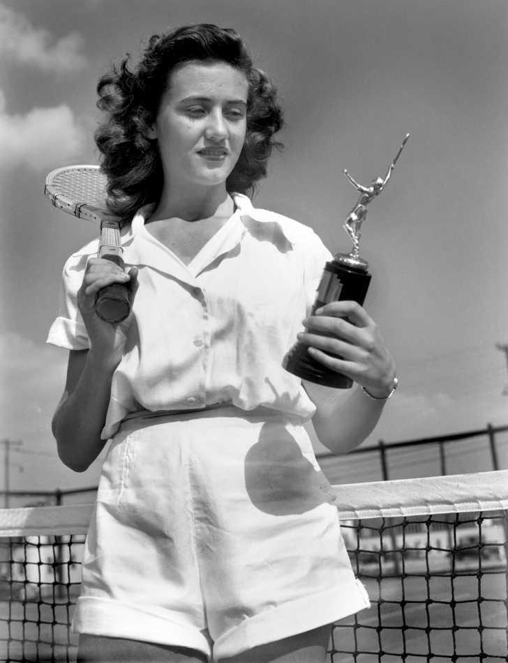 high school tennis player holding a trophy