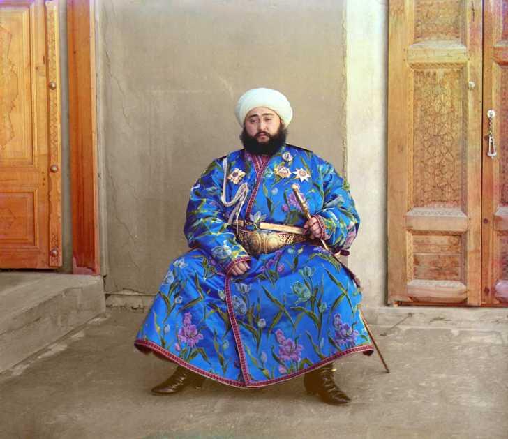 Alim Khan, Emir of Bukhara, seated holding sword.