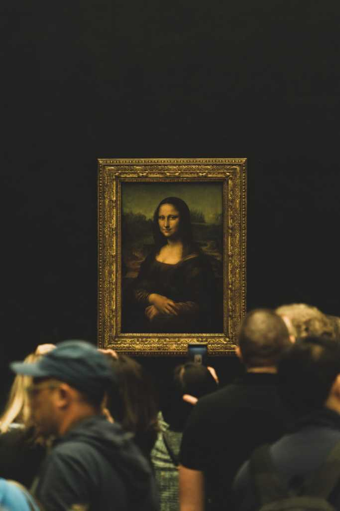 the Mona Lisa surrounded by visitors to the Louvre