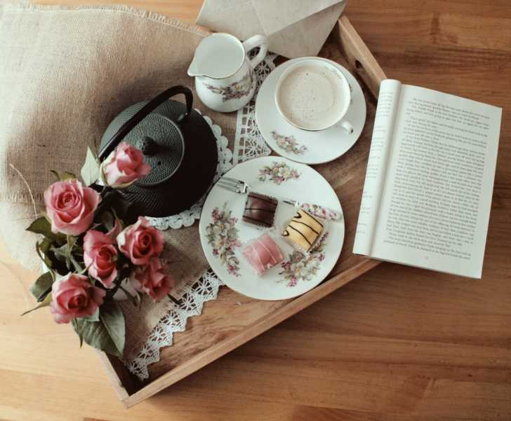 tray with teacup, chocolates, book, and flowers