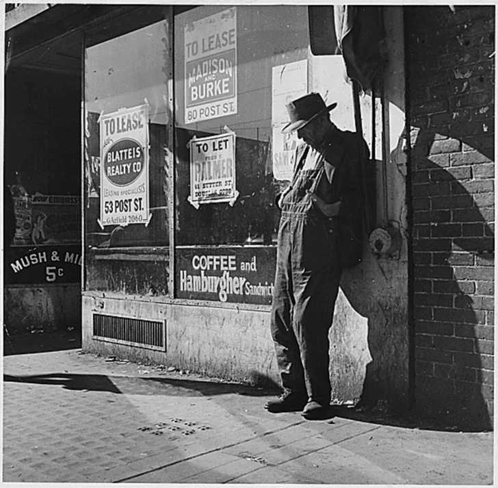 unemployed man loitering outside a shuttered general store, 1935