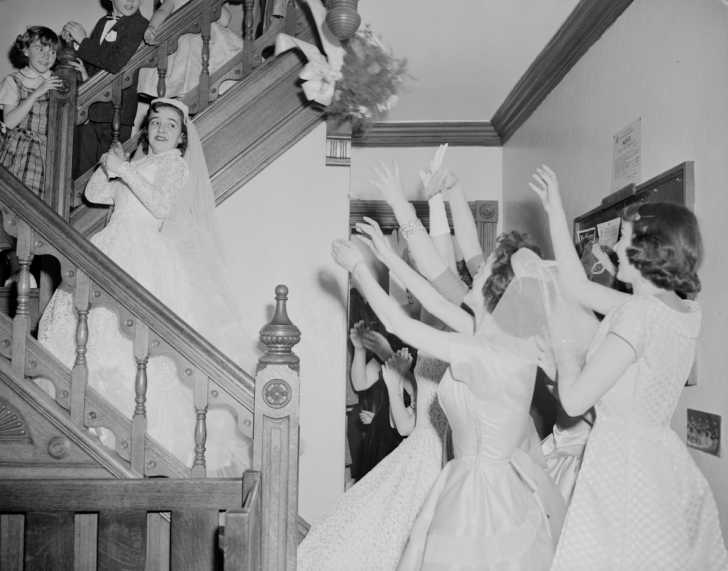 1950s bride throwing her bouquet on a set of stairs