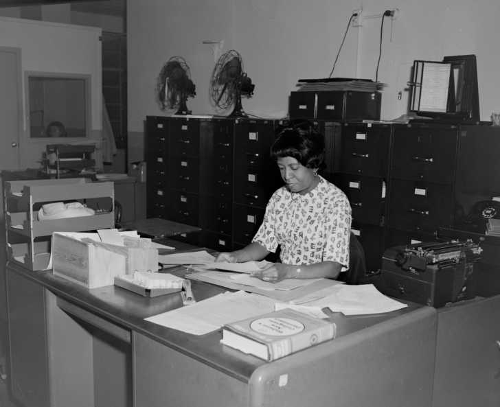 woman working at a desk in an office in the 1960s